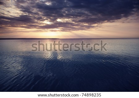Sunset at the sea. Horizontal photo with natural light and darkness - stock photo