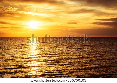 sunset at the sea with beautiful orange water and clouds - stock photo
