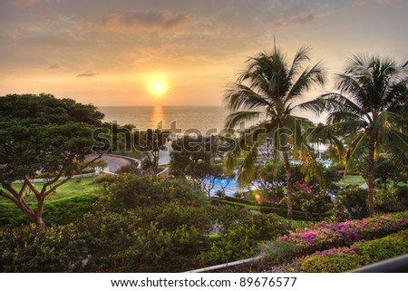 Sunset at tropical resort with view of ocean and lush garden. - stock photo