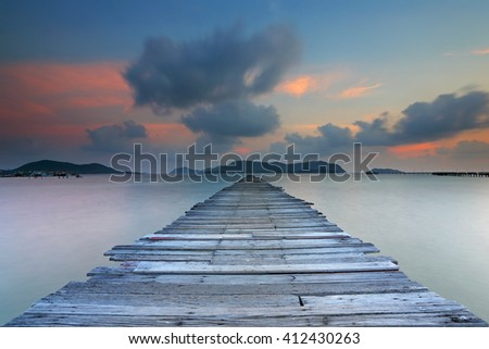 Sunset at wooden bridge on the sea with clouds moving in the sky background - stock photo