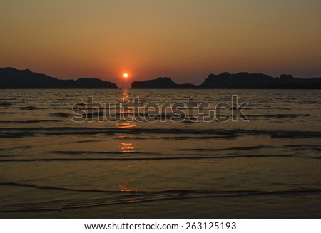 Sunset behind island at pakbara beach Thailand - stock photo