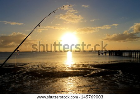Sunset behind jetty and fishing rod on Fraser Island, Queensland, Australia. - stock photo