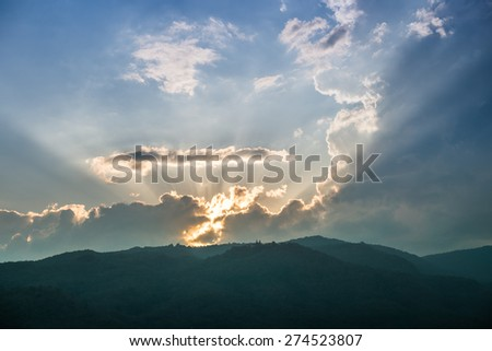 Sunset behind mountain with beautiful sunbeam through the cloud - stock photo