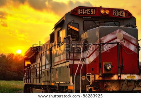 Sunset behind red and gray locomotive - stock photo