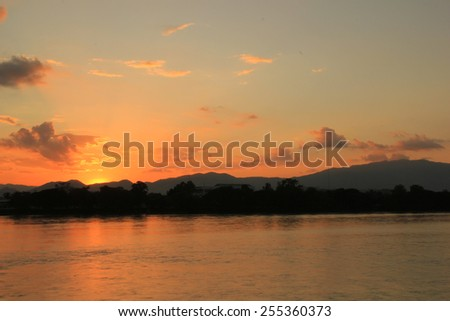 Sunset behind the mountain - stock photo