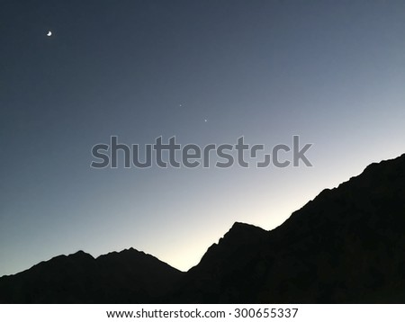 Sunset behind the Mountains of Sinai, Egypt during Ramadan.  Crescent moon , Venus and Jupiter in a line visible against a deep blue  sky and black silhouetted mountains.  Background  room for text.   - stock photo