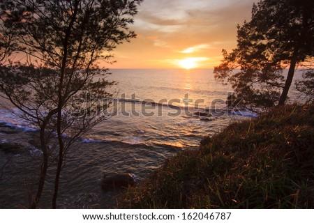 sunset between trees at the Tip of Borneo, Sabah, Malaysia - stock photo