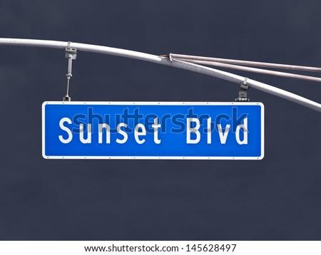 Sunset Blvd overhead street sign with dark storm sky. - stock photo