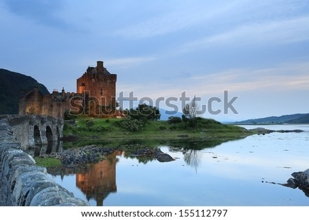 Sunset by Eilean Donan Castle, Scotland with crystal clear reflections in Loch Dornie - stock photo