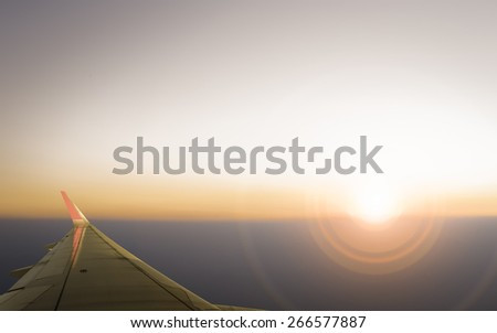 Sunset, cloudy sky and airplane wing as seen through window of an aircraft. - stock photo