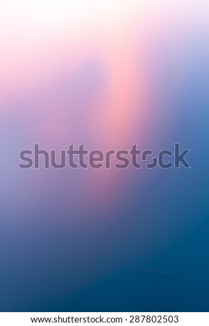 Sunset colored clouds reflecting in calm water abstract background colors transition pale pink through beep blue diagonally, vertical composition - stock photo