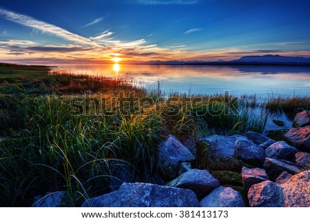 Sunset creating a multicoloured scenery, rocks on the foreground, mountains in the horizon, airy clouds - stock photo
