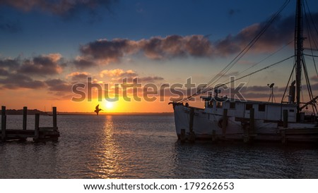 Sunset from Amelia Island, framed by Pier and Shrimp Trawler, with Pelican in Flight Silhouetted Against Colorful Sky - stock photo