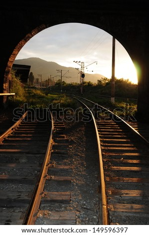 Sunset illumination on the railroad tracks - stock photo