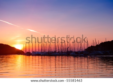 Sunset in Adriatic sea bay. Yacht silhouettes and calm water in sunset light - stock photo