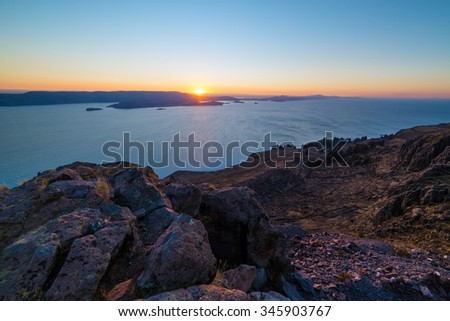 Sunset in backlight from Amantani' Island Titicaca Lake, scenic travel destination in Peru. Sun beyond the headland with glowing marsala toned rocks in the foreground. Ultra wide angle view from above - stock photo