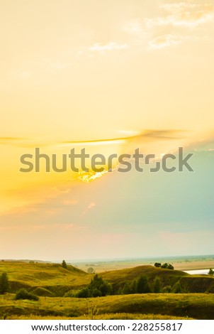 Sunset in countryside. Colorful landscape with trees, hills, river and cloudscape - stock photo