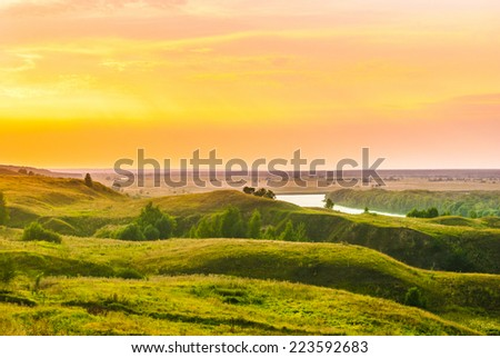 Sunset in countryside. Colorful landscape with trees, hills, river and cloudscape, unfocused - stock photo