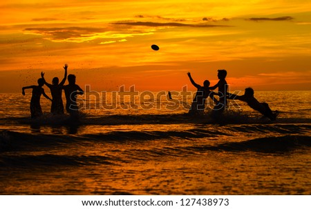 Sunset in January at Ft Meyers Beach in Florida.  A group of teens playing water football after sunset at Ft Meyers Beach in January. - stock photo