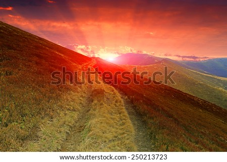 Sunset in mountains over rut road - stock photo