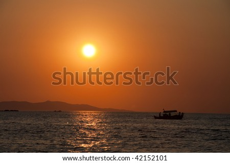 Sunset in Mykonos with a boat in front - stock photo