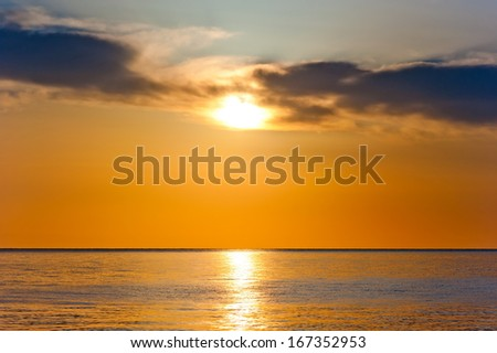 sunset in orange tones over a calm sea - stock photo