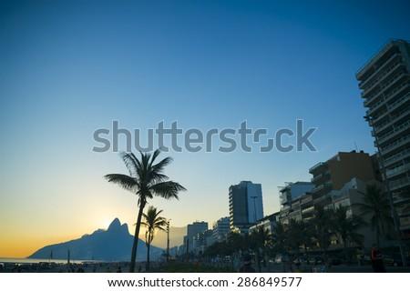 Sunset in Rio de Janeiro Ipanema Beach Brazil with city skyline next to Two Brothers Dois Irmaos Mountain and palm tree silhouettes - stock photo