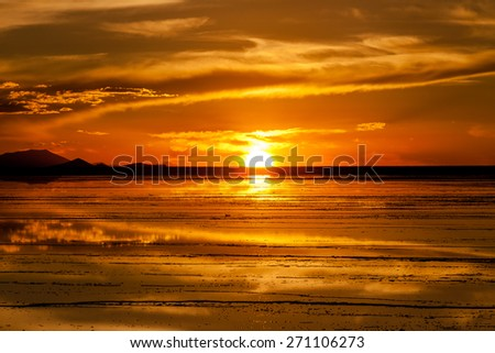 Sunset in salar de Uyuni. Reflection of the sun in the wet surface of salt. Mountain background - stock photo