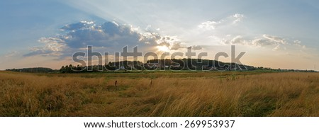 Sunset in the countryside. Panoramic rural landscape with a beautiful sky and sunshine. - stock photo