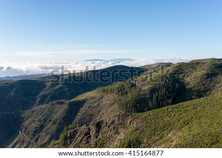 Sunset in the highlands of La Gomera. View direction Valle Gran Rey. In the background the Island La Palma. Clouds from trade winds over the mountains on La Gomera. The clouds comes from the Azores - stock photo