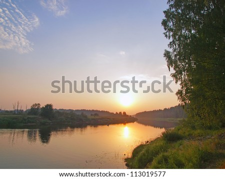 Sunset in the hot summer evening on the river - stock photo