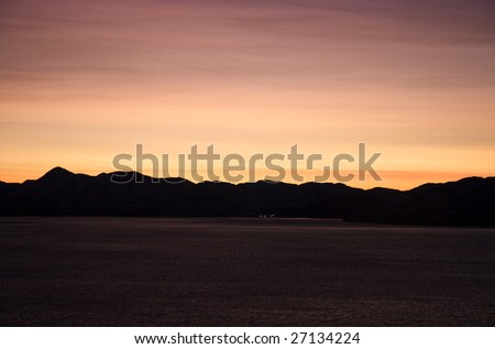 Sunset in the midwinter in Porsangerfjord - stock photo