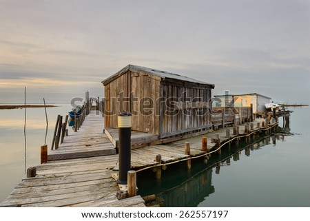 Sunset in the old artisanal fishing pier of Carrasqueira. Structure handmade in wood, is an amazing tourist attraction in the Alentejo coast. Landscape to convey peace and great beauty. - stock photo