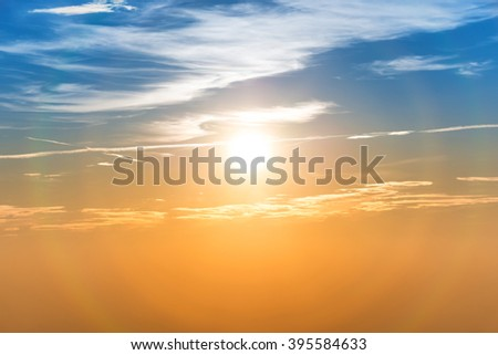 Sunset in the sky with blue orange clouds and big sun - stock photo