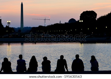Sunset in Washington D.C. with silhouette of Washington Monument and people around Capitol Building reflection pool - stock photo