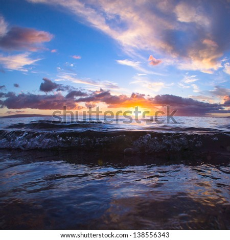 Sunset into the pacific ocean over beautiful Maui, Hawaii - stock photo