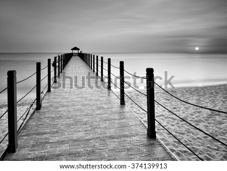 Sunset jetty in black and white. - stock photo