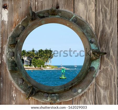 Sunset Key, Key West, Florida, as seen through a rustic old porthole. - stock photo
