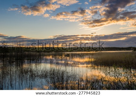 Sunset landscape at the calm weather lake with dramatic colorful sky and cloud reflections on the water. - stock photo