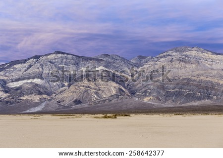 Sunset landscape in Death Valley national park. Colorful stripped mountains in desert with purple sky. Death Valley national park, California - stock photo
