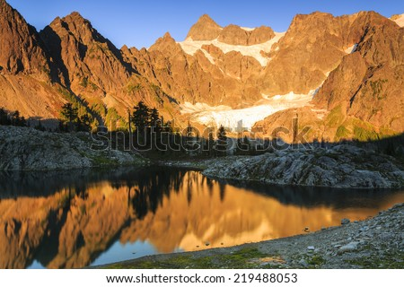 Sunset landscape of rocky mountains reflecting on a shallow lake - stock photo