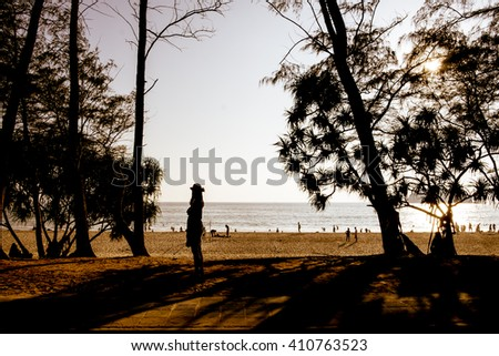 Sunset of seascape with silhouette tree in the foreground in the distance with beautiful lighting and orange  - stock photo