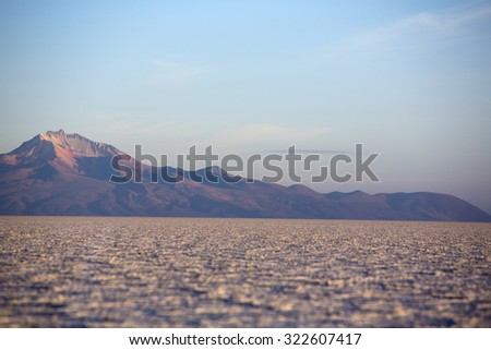 Sunset of the Salar of Uyuni during the dry season with very low angle, the salt plains are a completely flat expanse of dry salt. Bolivia - stock photo