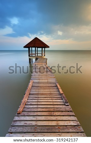 Sunset of wooden landing with pavilion in the sea at Black Sand Beach, Trat Province of Thailand - stock photo