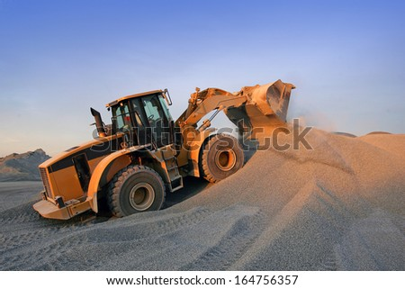 sunset on a bulldozer in action - stock photo