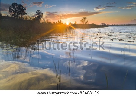 Sunset on a lake with reflection of sky in the water - stock photo