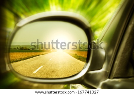 Sunset on a lonely country road, as seen in car mirror. - stock photo