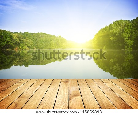 Sunset on forest lake and wooden board background - stock photo