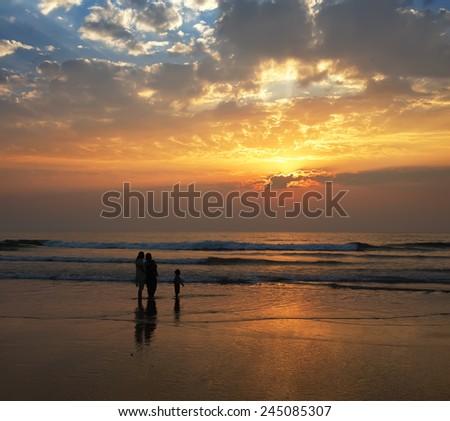 sunset on Goa sand beach with family silhouettes  - stock photo