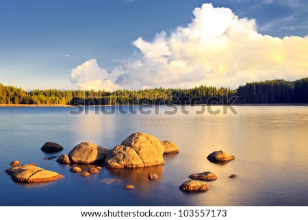 sunset on lake with stones - stock photo